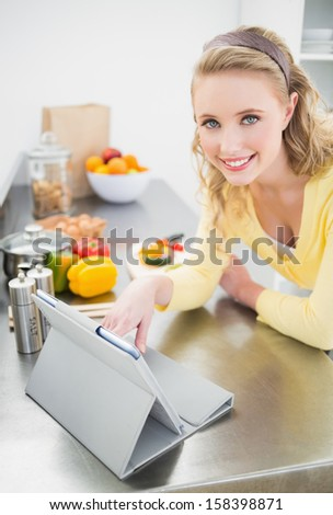 Cheerful cute blonde using tablet in bright kitchen - stock photo