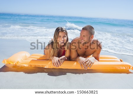 Cheerful cute couple in swimsuit lying on the beach together - stock photo
