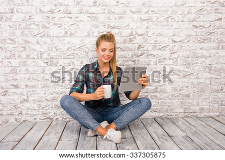 Cheerful cute girl with tablet and cup sitting on the floar