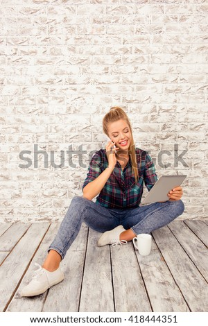 Cheerful cute girl with tablet and cup sitting on the floor talking on the phone