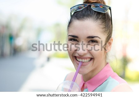 Cheerful cute hipster woman in the street with Iced Latte coffee smiling - stock photo