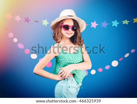 Cheerful cute little girl in sunglasses standing and posing over blue background