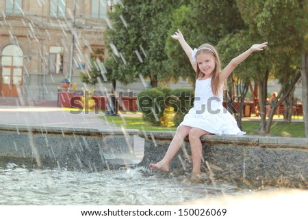 Cheerful cute little girl in white dress sitting near the fountain and smiling at summer theme - stock photo