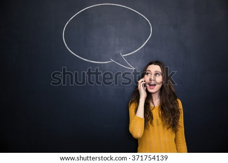 Cheerful cute lovely young woman talking on cell phone over blackboard with blank speech bubble - stock photo