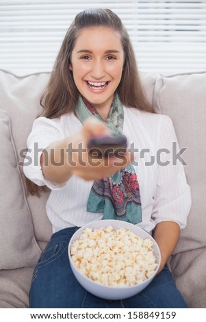 Cheerful cute model on cosy sofa changing tv channel - stock photo