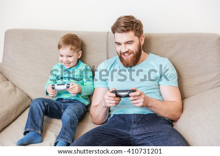 Cheerful dad and son playing computer games together at home - stock photo