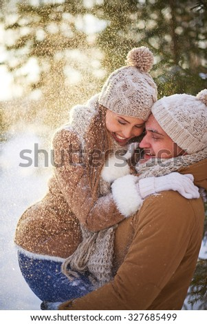 Cheerful dates having fun in snowfall - stock photo