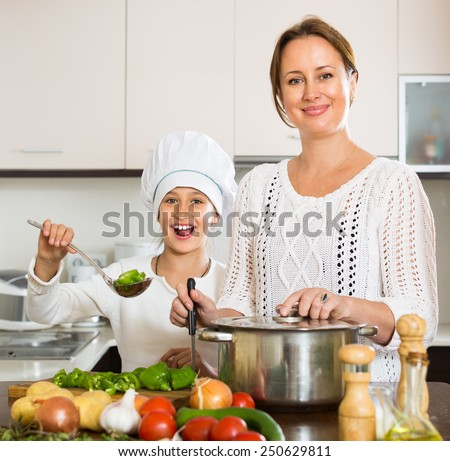 Cheerful daughter and happy mom with vegetables and casserole at domestic kitchen - stock photo