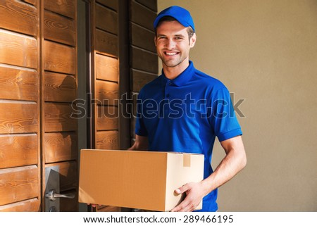 Cheerful delivery man. Happy young courier holding a cardboard box while standing against door of residential house  - stock photo