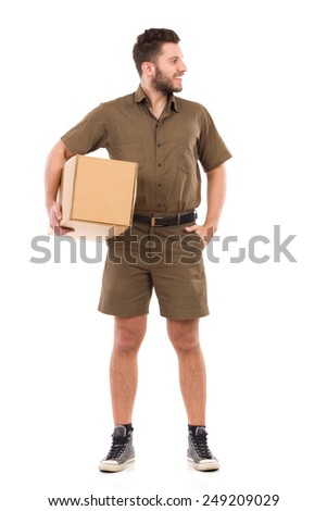 Cheerful delivery man standing and holding carton box under arm. Full length studio shot isolated on white. - stock photo