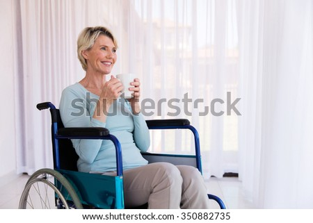 cheerful disabled woman holding hot coffee cup at home - stock photo