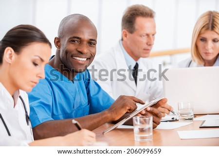Cheerful doctor at the meeting. Handsome young African doctor smiling while sitting together with his colleagues at the meeting - stock photo