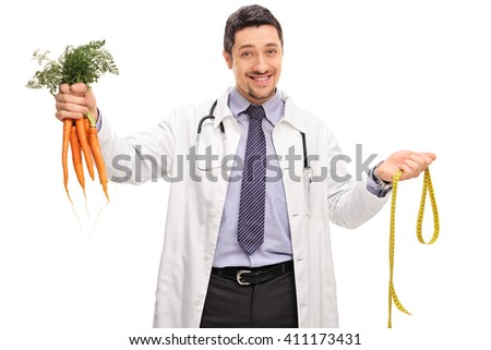 Cheerful doctor holding a bunch of carrots and a measuring tape isolated on white background