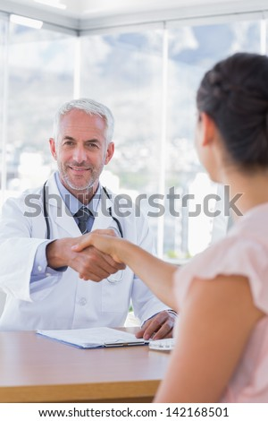 Cheerful doctor shaking hands to patient in the office - stock photo