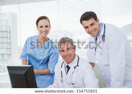 Cheerful doctors and surgeon looking at camera while working together in bright office
