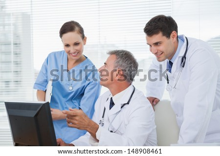 Cheerful doctors and surgeon working together on computer in bright office - stock photo