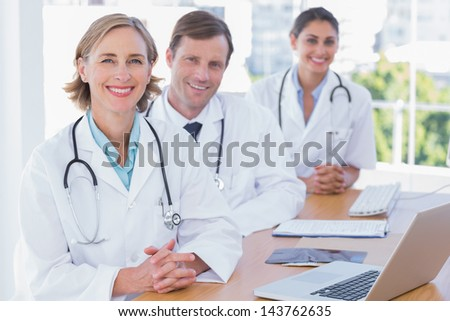 Cheerful doctors posing at their desk with a laptop computer