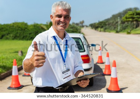 cheerful driving school instructor thumb up - stock photo