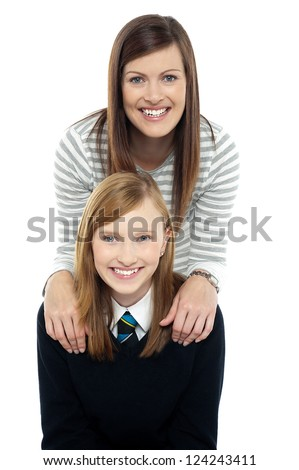 Cheerful duo of adorable mother and daughter. Mom in trendy outfit and girl in school uniform. - stock photo