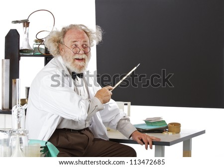 Cheerful eccentric senior scientist in his lab points to blackboard and explains his ideas. High key, horizontal, copy space. - stock photo
