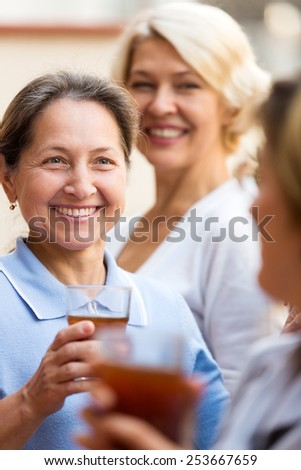 Cheerful elderly female colleagues having lunch break at patio - stock photo
