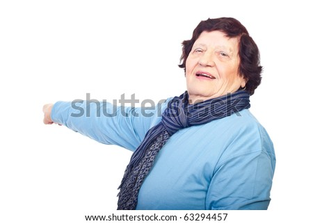 Cheerful elderly woman pointing to copy space on  white background - stock photo