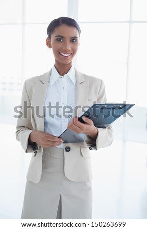 Cheerful elegant businesswoman in bright office holding clipboard - stock photo