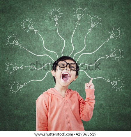 Cheerful elementary school student standing in the class with branching light bulb. Concept of a branching mind - stock photo