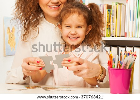 Cheerful elementary school teacher and her pupil - stock photo