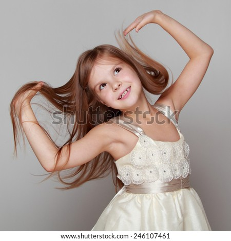 cheerful emotional little girl in a beautiful dress is dancing and having fun  - stock photo