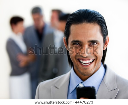 Cheerful ethnic businessman sending a text with his team in the background - stock photo