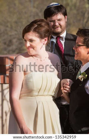 Cheerful European woman with bride and rabbi outdoors - stock photo