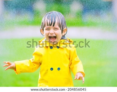 Cheerful, excited baby having fun, running wet under rain, summertime - stock photo