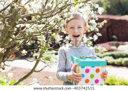 cheerful excited little boy holding gift box for mother's day in the blooming park at spring time - stock photo