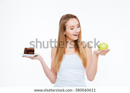 Cheerful excited young woman choosing between healthy and unhealthy food over white background - stock photo