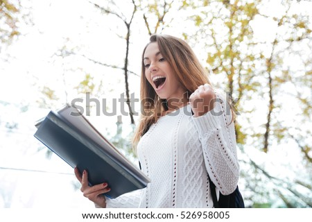 Cheerful excited young woman with notebook shouting and celebrating success outdoors