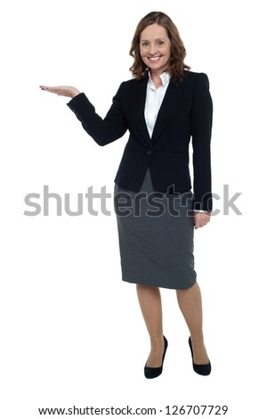 Cheerful executive presenting copy space with open palm. Full length shot. - stock photo
