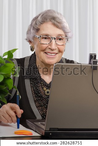 Cheerful experienced teacher looking at web camera on laptop monitor. Smiling old woman is teaching on-line English (or any) language. Vertical portrait. - stock photo