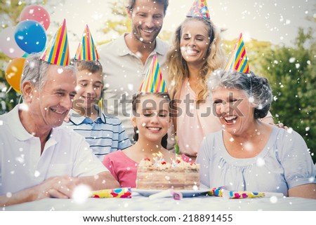 Cheerful extended family celebrating a birthday against snow falling - stock photo