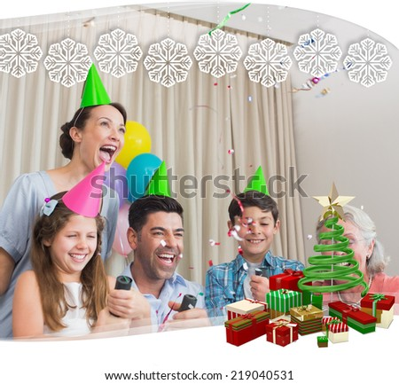 Cheerful extended family playing with Christmas crackers against snowflake frame - stock photo