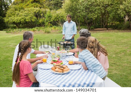 Cheerful extended family sitting at picnic table watching father at the barbecue - stock photo