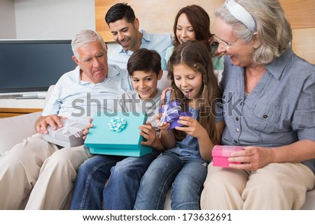 Cheerful extended family sitting on sofa with gift boxes in the living room at home