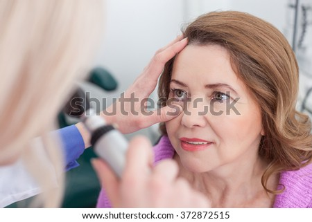 Cheerful eye doctor is working with a patient - stock photo