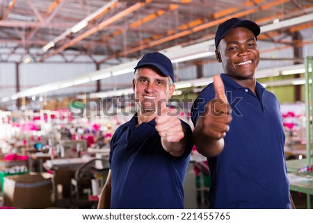 cheerful factory supervisors giving thumbs up - stock photo