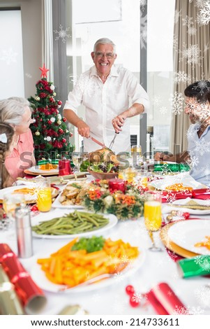 Cheerful family at dining table for christmas dinner against snow falling - stock photo