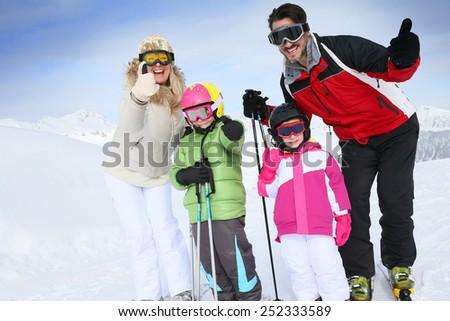 Cheerful family at ski resort showing thumbs up - stock photo