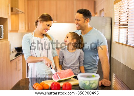 cheerful family cutting watermelon at home - stock photo