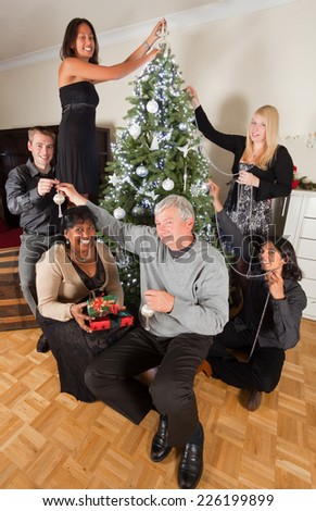 Cheerful family decorating the christmas tree together - stock photo