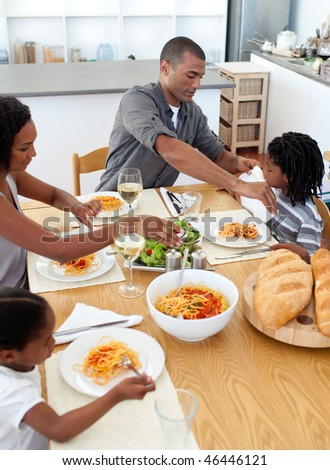Cheerful family dining together in the kitchen - stock photo