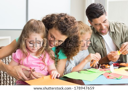 Cheerful family doing arts and crafts together at the table at home in kitchen - stock photo